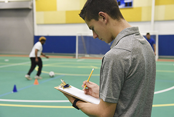 Physical Education Student writing on clipboard