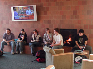 Students sitting by fireplace