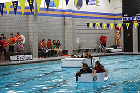 Students in boats competing in pool