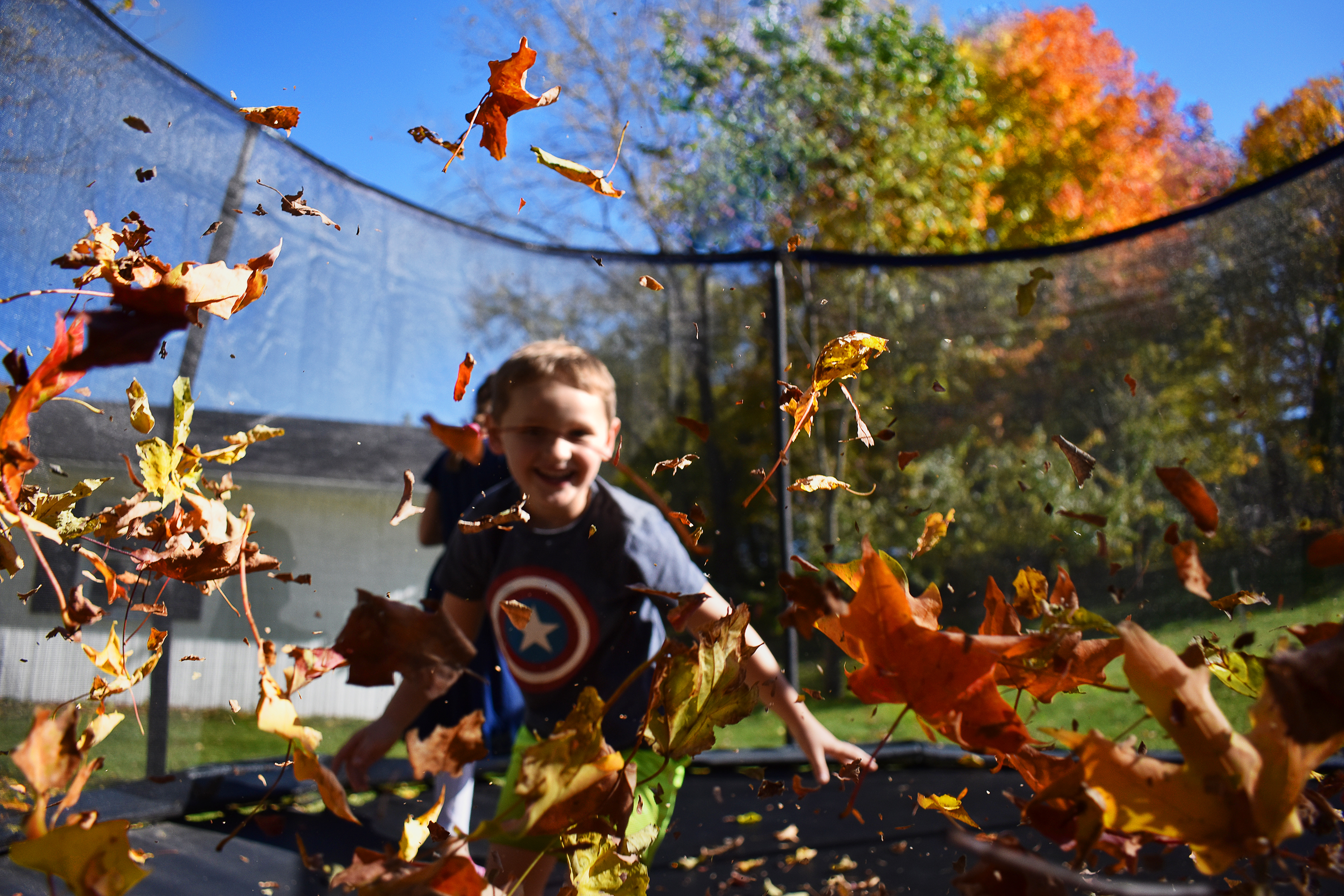 child jumping and fall leaves